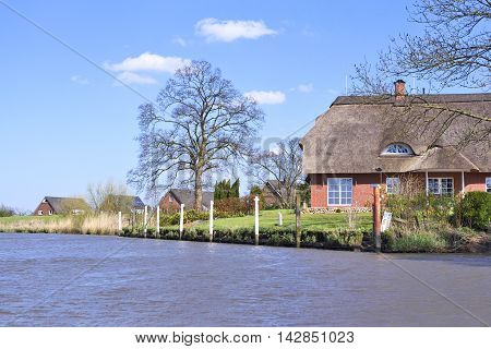Idyllic river scene in winter with cottages and bare trees.