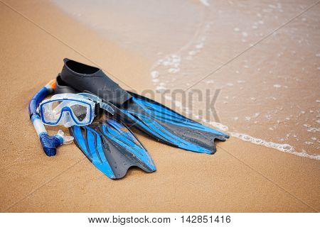 Swim flippers mask snorkel in the surf on the sandy beach; selective focus