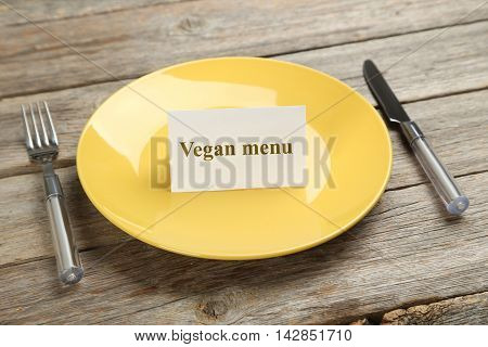 Yellow plate on a grey wooden table, vegan menu