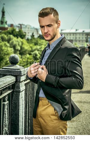 Elegant well-dressed man standing on the bridge in the city center. Beauty, fashion. Business style.
