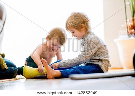 Boys Sitting On The Floor Playing On Tablet.