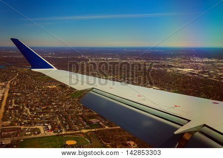Wing of an airplane flying above the clouds and ground sky flying ground