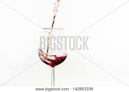 red wine is splashing into a wine glass