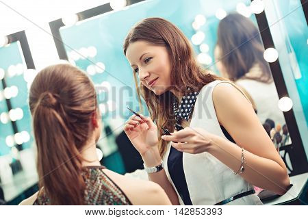 Make-up artist and model at work in front of mirror