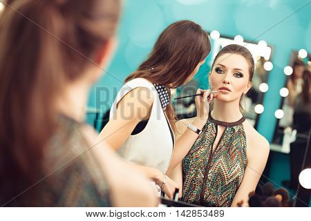 Make-up artist applying lipstick with a brush on model's lips selective focus on model's reflection