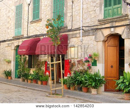 Historic city or old town with lovely bakery with red sun blinds.