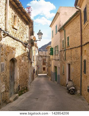 Spanish village with narrow, idyllic street, motorcycle and antique street light.