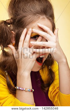Young shy woman covering her face with hands and looking through her fingers