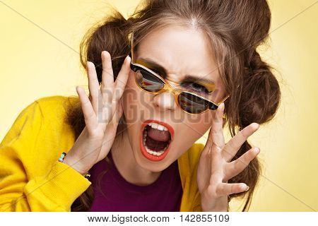 Excited young girl wearing retro sunglasses on yellow background