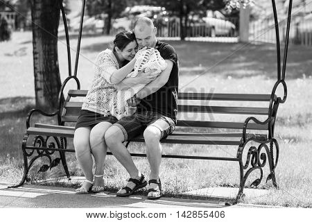 Young Family Sitting On A Park Bench. Father Holding Newborn Daughter In Her Arms.black And White Ph