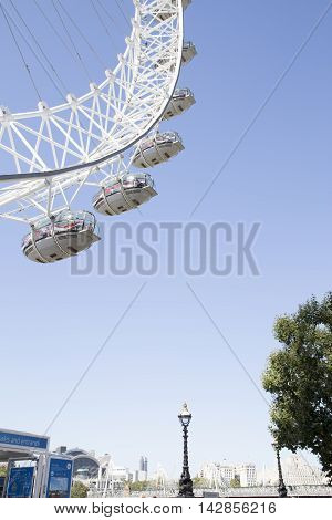 LONDON UK - AUG 12 2016: Coco Cola London Eye framed in top left corner with blue sky and london city sky line with tree and lamps.