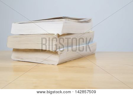 Three books in a pile on a wooden table