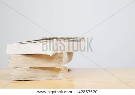 Paper back books in a pile on wooden table