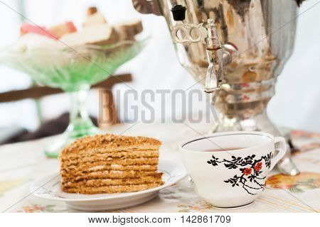 Piece Of Cake Honey Cake On A Plate, A Cup Of Tea And A Samovar