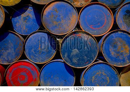One red fifty gallon steel drum  and blue barrels