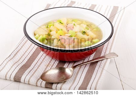 warm vegetable soup with potatoes celery and bacon cubes in a red enamel bowl