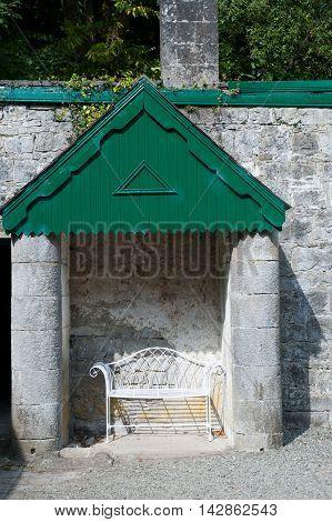 Single white metal bench in the garden