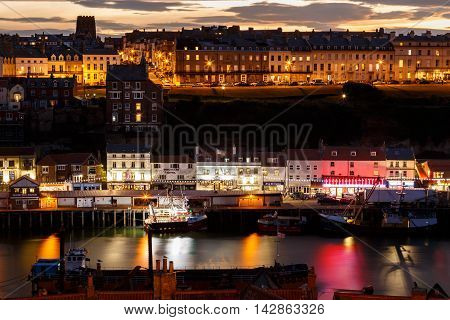WHITBY NORTH YORKSHIRE - AUGUST 12: Whitby harbour and town at night with a dramatic sunset behind. In Whitby North Yorkshire England. On 12th August 2016.