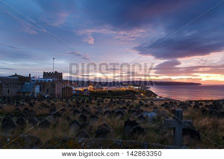 WHITBY ENGLAND - AUGUST 12: Whitby St Mary's church and graveyard against a dramatic sunset. In Whitby North Yorkshire England. On 12th August 2016