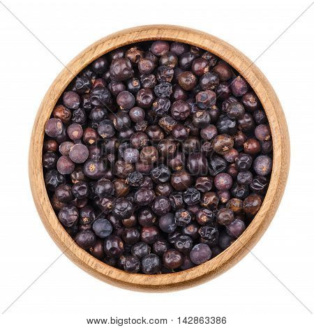 Juniper berries in a bowl on white background. Dried seed cones from Juniperus communis, a conifer, are used as spice and give gin its flavor. Isolated, macro photo and close up from above.