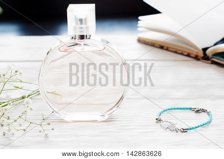 Bottle of nameless perfume on female table with different staff. Diary, handmade bracelet and vial of essence on white wooden table. Feminine workplace