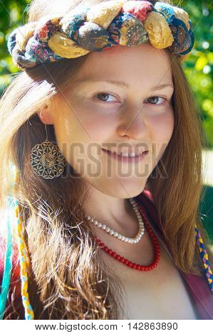 Girl with brown hair in a clothes in boho style, in red and white the necklace with colorful braids and a rim of tissue