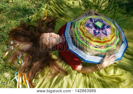 girl with brown hair in a long green skirt lies on the grass with big wicker native american mandala