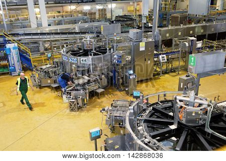 ST. PETERSBURG, RUSSIA - AUGUST 11, 2016: Worker at beer conveyor in the Heineken brewery. It was the first Heineken brewery in Russia, and now it can produce over 5 millions HL of beer per year
