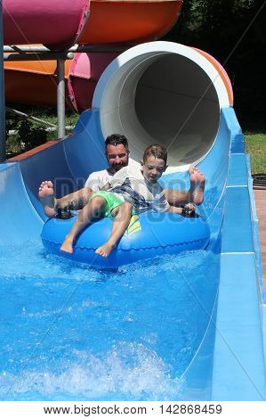 A father and son having fun on a water slide in a waterpark while on vacation in turkey, 2016