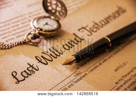 Vintage / retro style with a long shadow : Fountain pen a pocket watch on a last will and testament. A form is printed on a mulberry paper and waiting to be filled and signed by testator / testatrix.