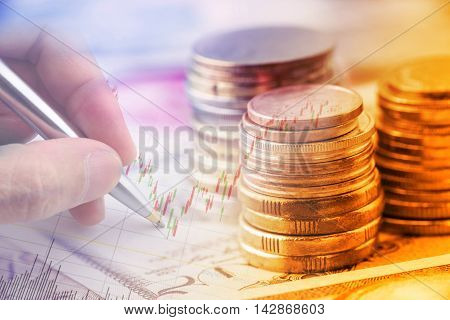 Closeup view : Stack of coins and a hand holding a ballpoint pen is examining a technical chart of financial instrument. An idea / concept of currency trading making a decision for an optimal gain.