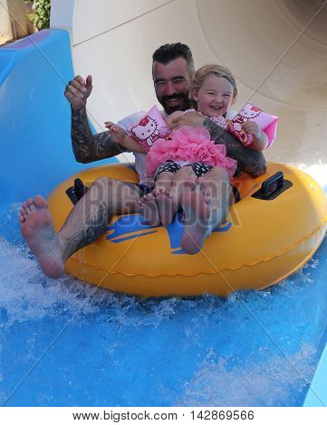 18TH JULY 2016,CALIS,TURKEY: A father and daughter having fun on a water slide in a waterpark while on vacation in calis, turkey,18th july 2016