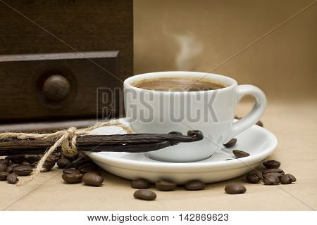 Coffee beans and vanilla on brown background