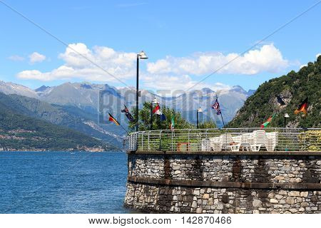 Different Flags At Village Varenna At Lake Como With Mountains In Lombardy, Italy