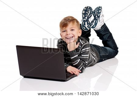 Happy boy lying on floor with laptop on white background