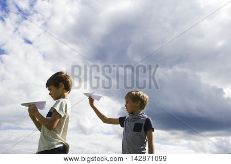 Little boys with paper planes against blue sky. Low angle view