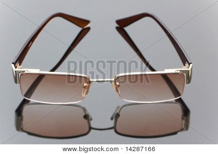 Stylish sun glasses on hifhly reflective background