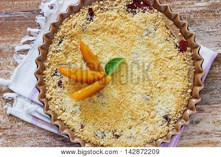 Plum crumble in a plate on the table. Traditional English cuisine. Top view
