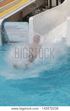 A man having fun on a water slide in a waterpark while on vacation in turkey, 2016