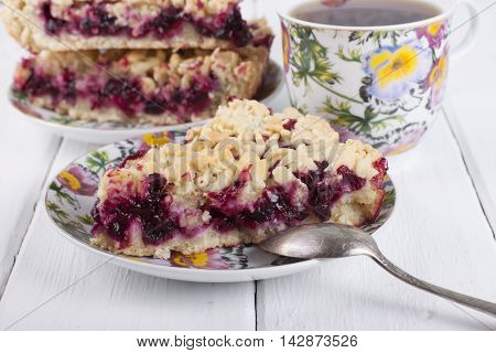 Shortcrust pie with berry filling. A piece of cake on a plate and cup of tea on a white table.