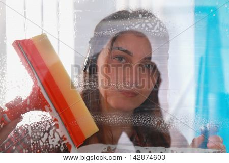Woman at work professional female cleaner cleaning and wiping window in office