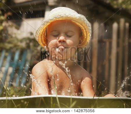 Little beautiful baby girl taking bath outdoors on the grass in vintage washing-up bowl (hygiene hardening nature)