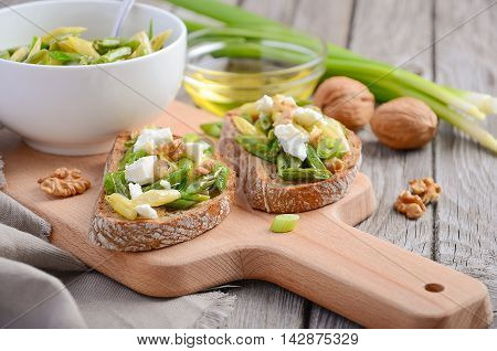 Bruschetta with french beans, green onions, feta cheese and walnuts, selective focus