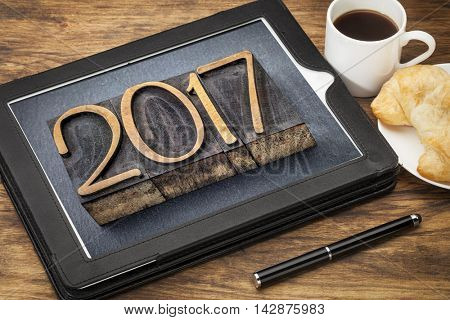 2017  - New Year concept  - number in vintage wood type printing blocks on a digital tablet with a cup of coffee