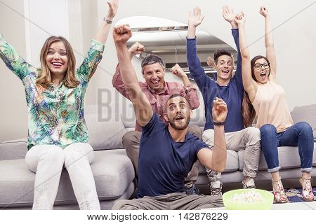 Group Of Friends Watching A Football Match On Tv On The Couch