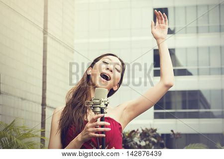 Asian Woman Singing And Raising Hands On The Rooftop Of The Building In Outdoor Scene
