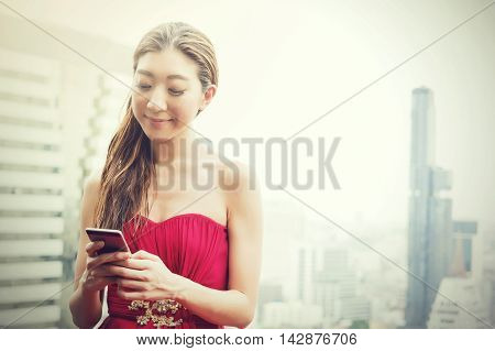 Happy Asian Woman Using Phone On Rooftop Of Building In Urban City Scene