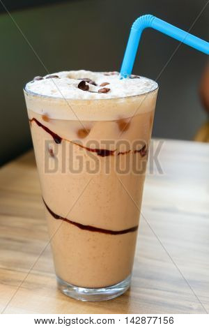 Iced coffee latte with chocolate sauce on wooden table