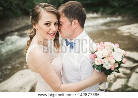 Happy wedding couple hugging and smiling each other on the background lake, forest.