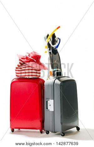 Suitcases with summer beach items over white background